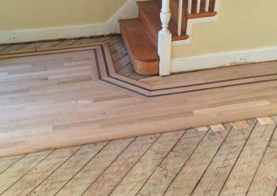 Custom installation of unfinished white oak with Peruvian Walnut border & fireplace frame & new slate tile