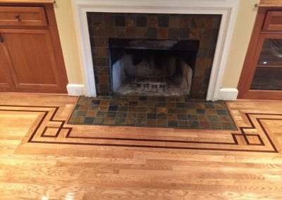 Custom installation of unfinished white oak with Peruvian Walnut border & fireplace frame & new slate tile